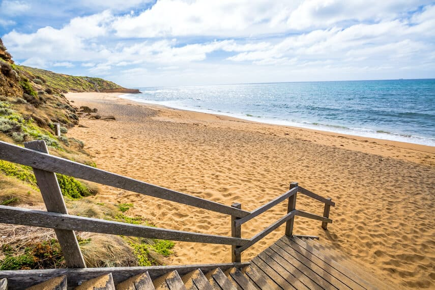 Wooden steps leading down to Bells Beach with the ocean on the right on the Great Ocean Road Australia