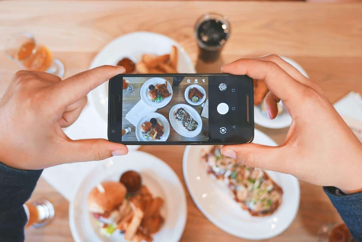 Cover photo for the Best Apollo Bay Restaurants, Bars & Cafes featuring 4 dishes on the table with a woman holding a mobile phone above to take a flatlay photo with the focus on the phone screen