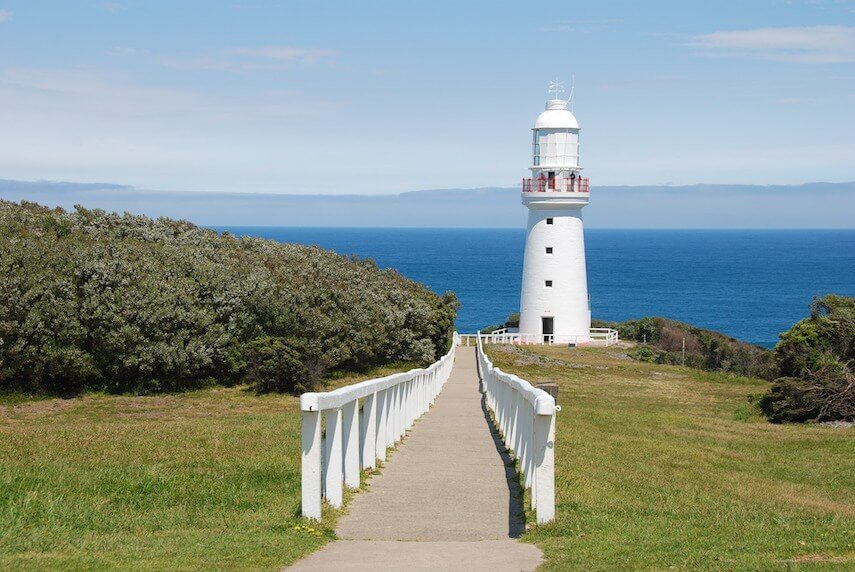 Cape Otway Lighthouse from the top of the white fences path leading down to it with the ocean in the background