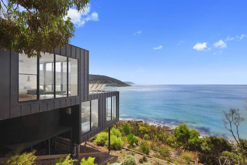 Side view of the multi story Cape Wye Holiday Home built into the hillside overlooking the ocean