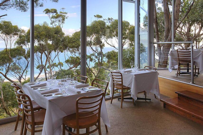 Interior of Chriss' Restaurant looking out over two wooden tables covered in white table cloths next to floor to ceiling windows overlooking the green treetops and blue ocean beyond