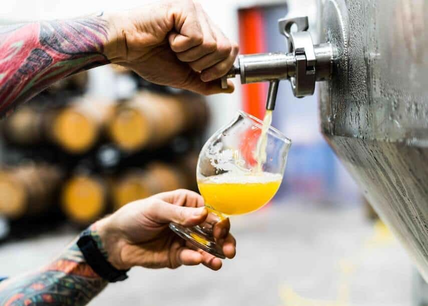 Close up shot of a mans tattooed arms and hands holding a pint pot on an angle while dispensing beer from a stainless steel keg