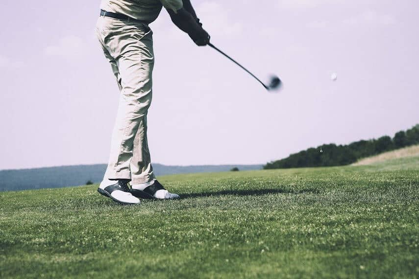 Photo of a golfer from the waist down wearing beige trousers with black and white golf shoes and a dark coloured jumper swinging a golf club