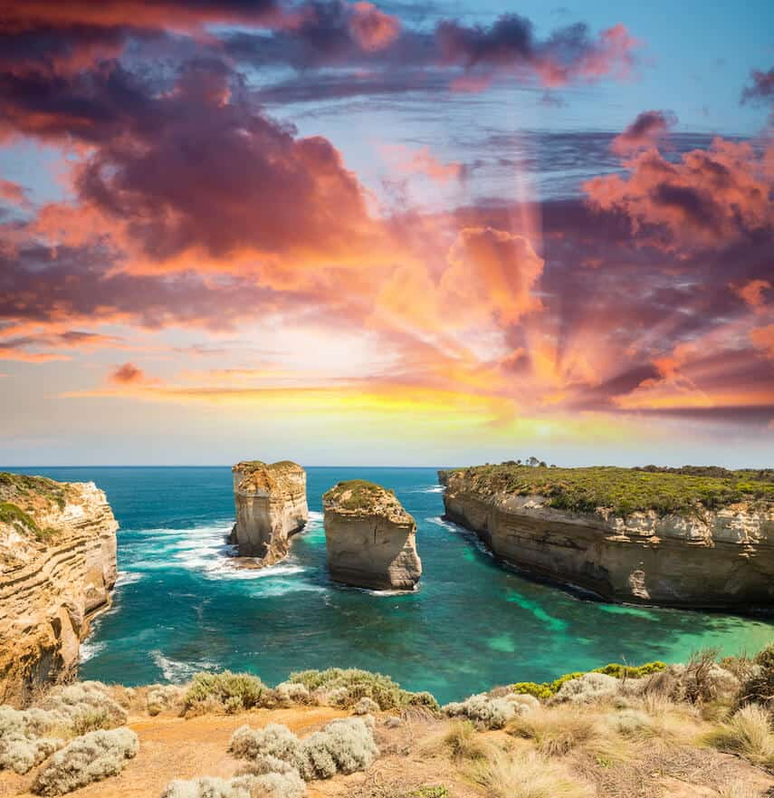 Cover Photo for 100+ Great Ocean Road Attractions featuring rock formations in the ocean surrounded by blue-turquoise water and underneath a pink sunset sky