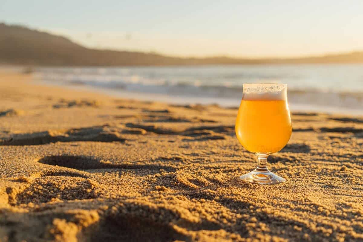 Great Ocean Road Breweries Cover Image with a Pint of Beer in focus on the Sand next to the ocean