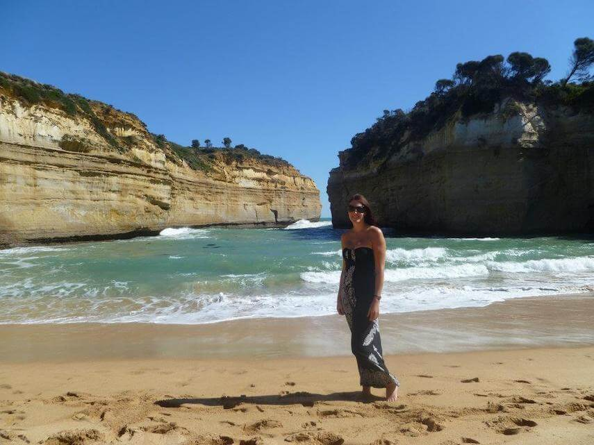 Girl in a black full length dress stood on the beach in front of the ocean between the towering rock formations of Loch Ard Gorge