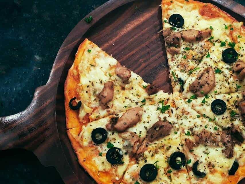 Pizza with a slice cut out on a circular wooden board on a black countertop