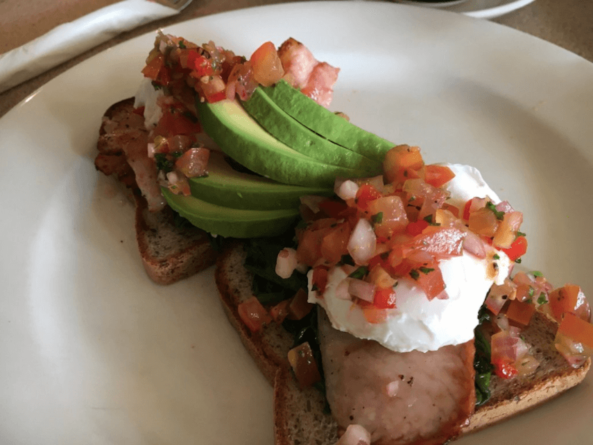 Toast topped with poached egg, bacon, avocado and bruschetta mix on a white plate at Sandy Feet Cafe Apollo Bay
