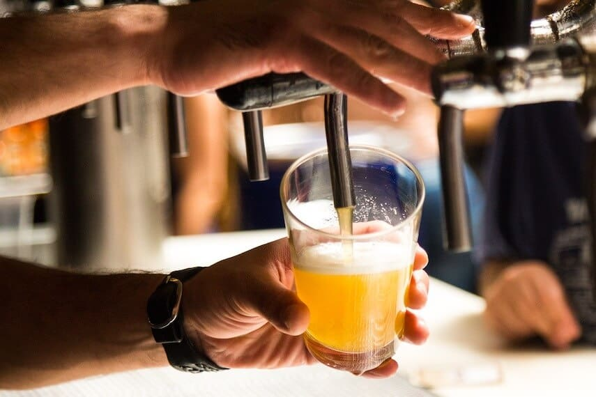 Close up shot of a mans hands holding a pint pot on an angle while dispensing beer from a pump