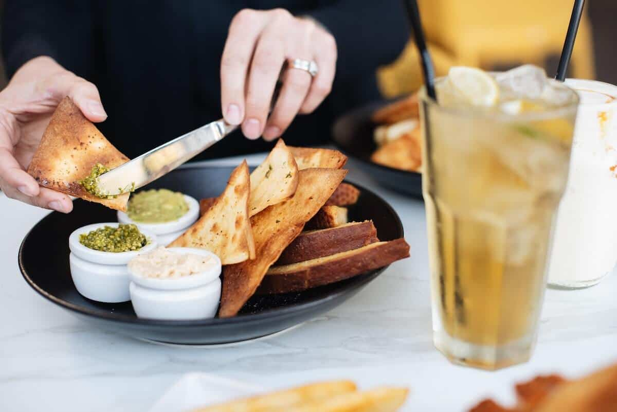 Top Torquay Restaurants cover photo of a man sitting at a table from the chest down putting dip and dukkah onto a slice of toasted bread, and a glass of ice tea with ice