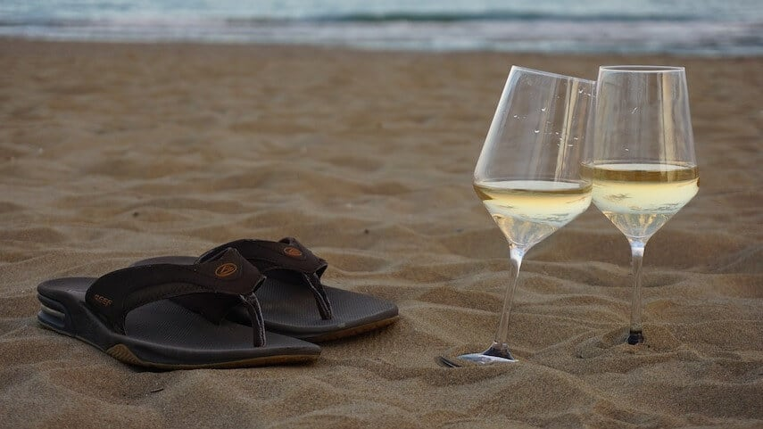 Two glasses of wine propped against each other on the beach next to a brown pair of flip flops with the ocean in the background