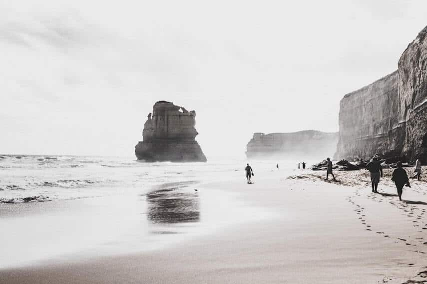 Cover photo for 5 Day Great Ocean Road Itinerary featuring Black and white image of the beach at Gibson Steps with a large limestone rock standing tall in the ocean and people walking on the sand towards it