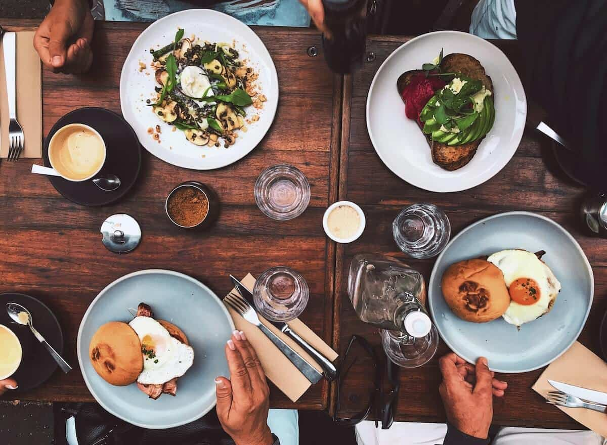 Cover photo for the Best Anglesea Restaurants, Bars & Cafes featuring a top-down shot of 4 plates of food on a table along with knives and forks, water glasses and salt and pepper shaker