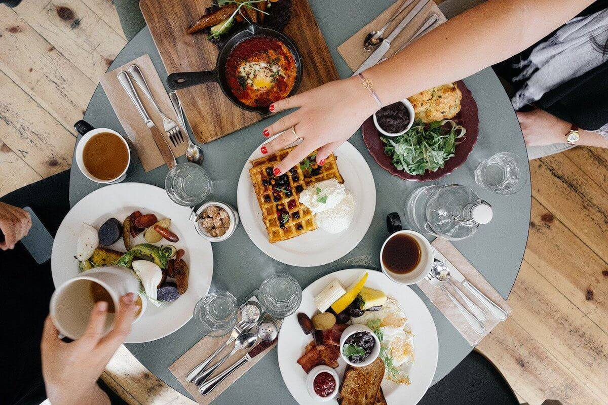 Cover photo for the Best Port Campbell Restaurants, Bars & Cafes featuring a top down shot of a table with 4 dishes on plates and 1 dish on a wooden board with a womans hand with red nail varnish reaching into the middle of the table