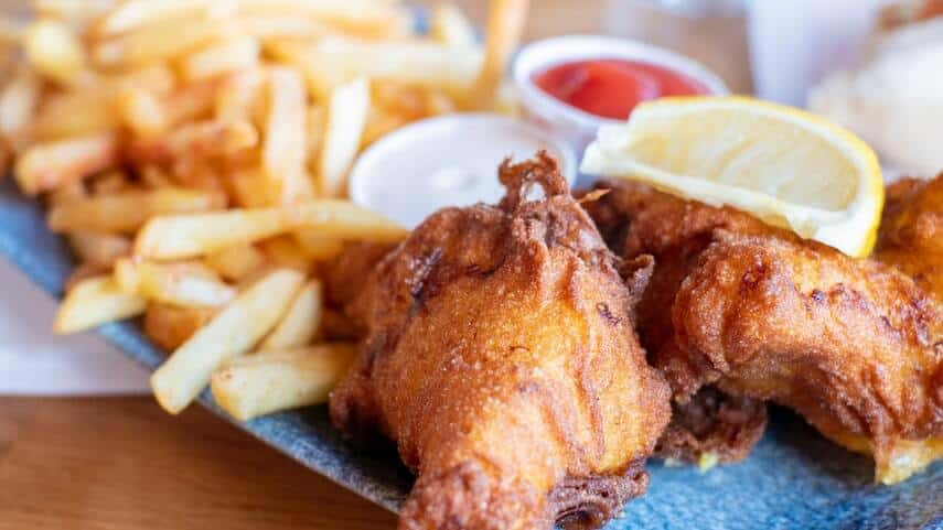 Fish and Chips on a plate topped with a slice of lemon with a small pot of tomato sauce between the fish and chips