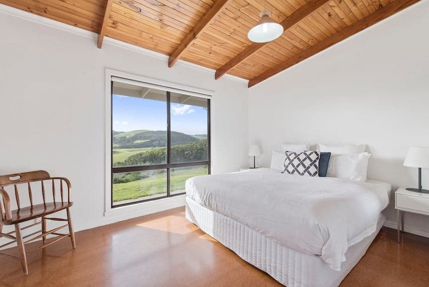 Bedroom containing double bed with white linen and large window with view of the countryside