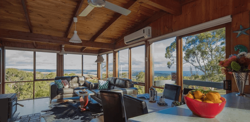 Inside of a wooden cabin with floor to ceiling windows wrapping around the room at Glenaire Cottages