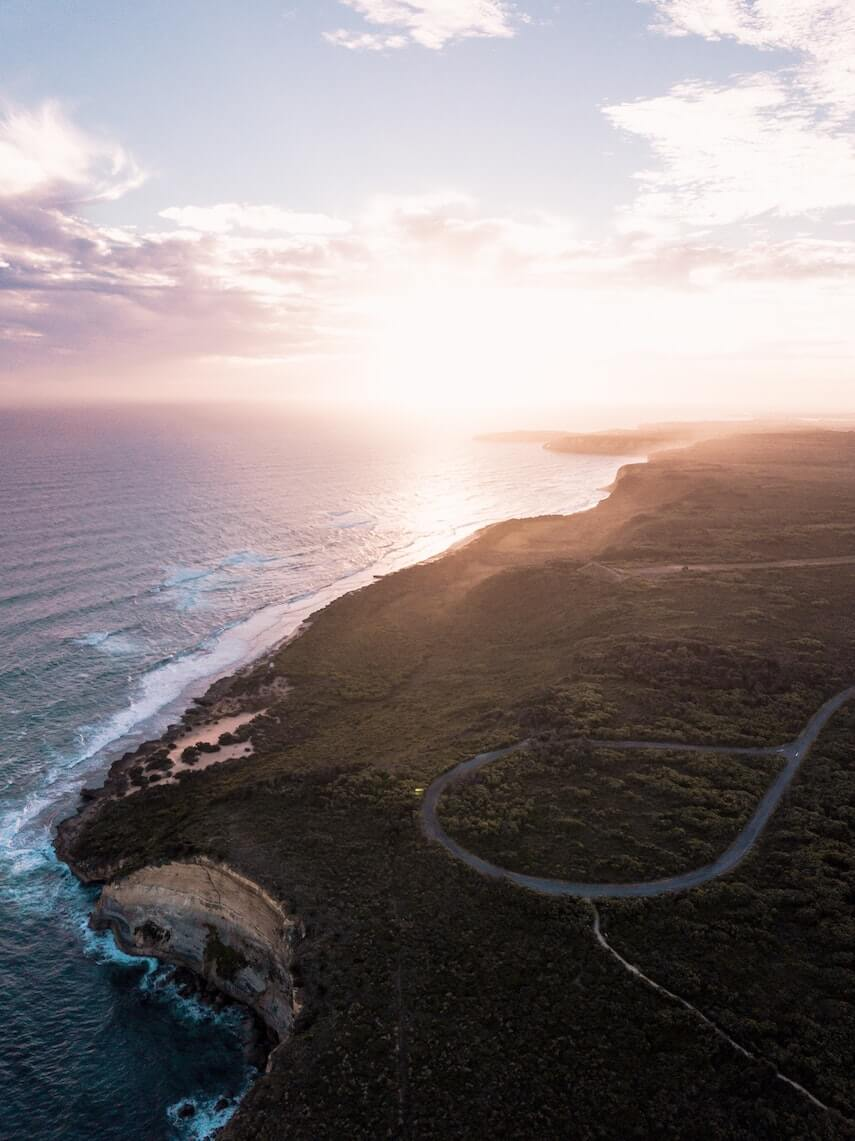 Great Ocean Road Itinerary Cover Shot featuring an aerial shot of a road winding along the cliff edge with the ocean below and the sunset in the background