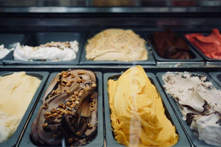 Different coloured and flavoured ice cream in black trays on display