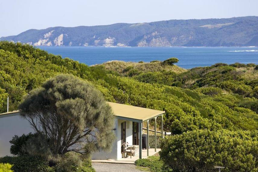 Johanna seaside cottage nestled in the green landscape, surrounded by trees with the ocean in the distance