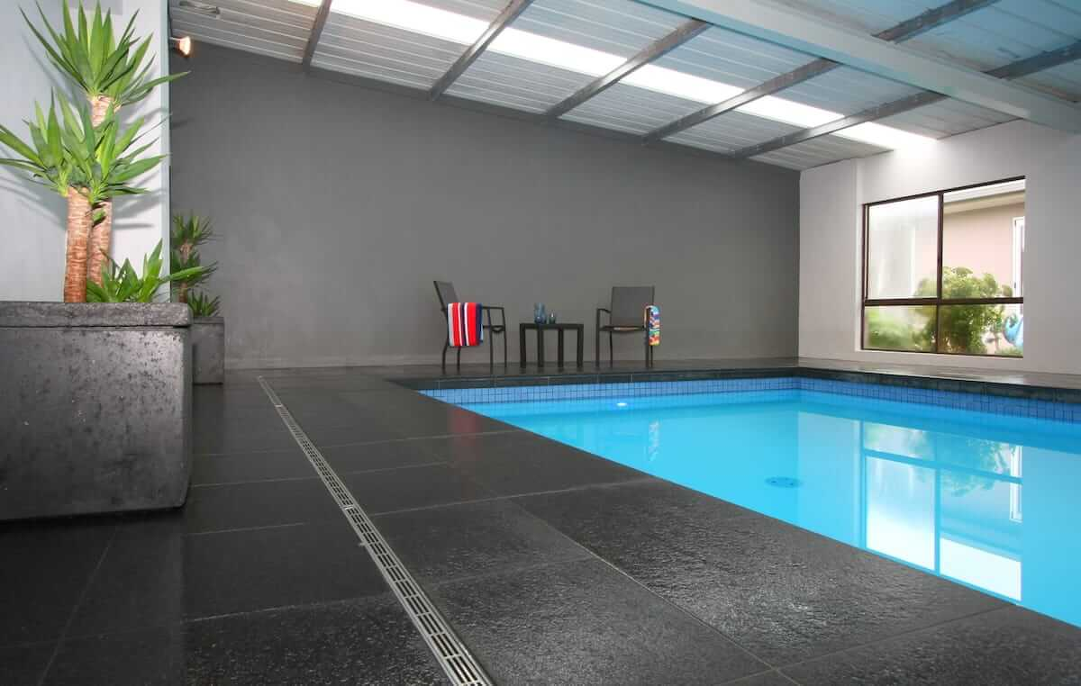 Indoor swimming pool surrounded by grey tiled floor