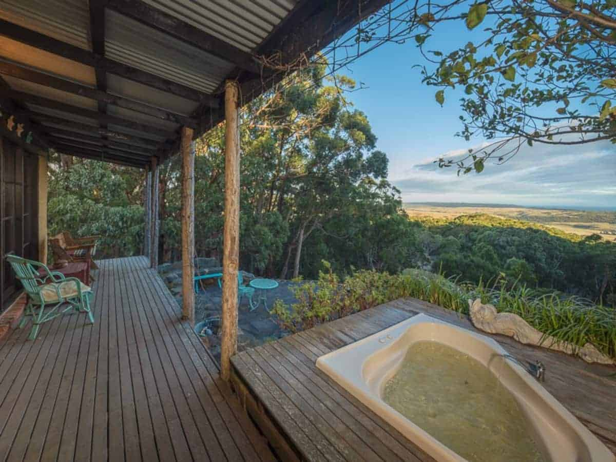 Wooden decking with a sunken hot tub looking out into the forrest