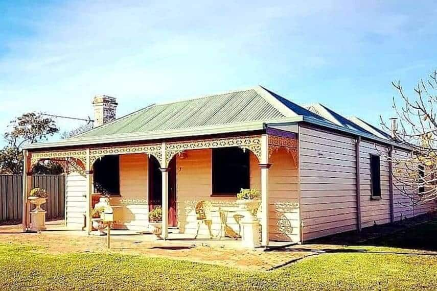 Dates exterior of Dusting Cottage - a white weatherboard single storey cabin with a green tin roof