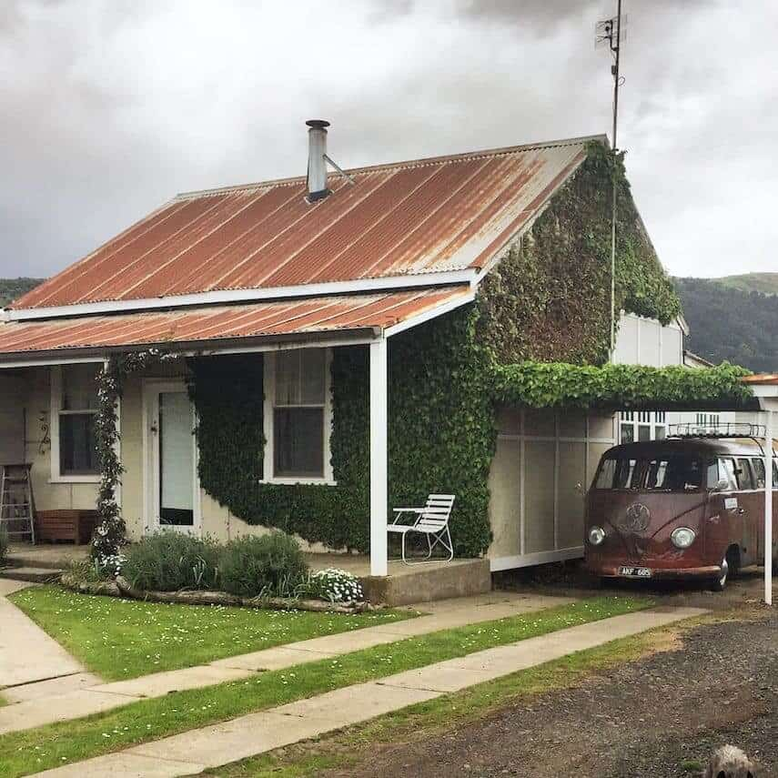 Exterior of Little Ivy Cottage with a battered and rusted VW campervan purked under the attached awning