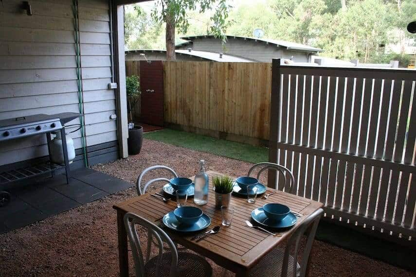 Fenced outdoor area of Lorne Surfdogz with table set for 4 in the foreground and BBQ to the back of shot