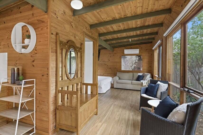 Interior shot of a wooden cabin with floor to ceiling widows on the right hand side