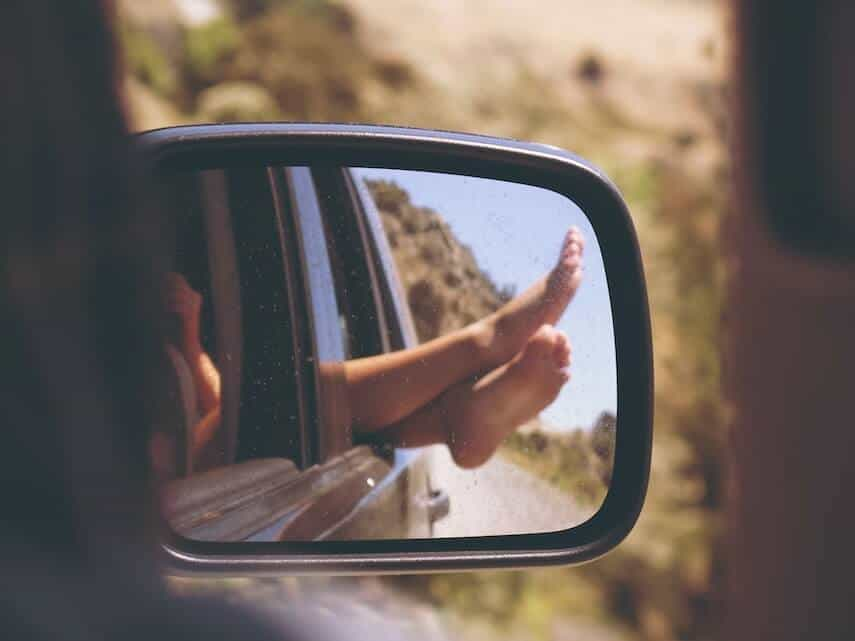 Photo of the wing mirror of of car reflecting legs crosses out of the window