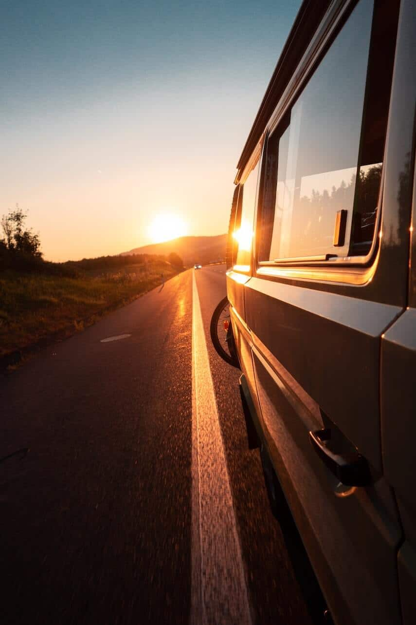 The Ultimate Travel Playlist pinnable image of a campervan driving into the sunset