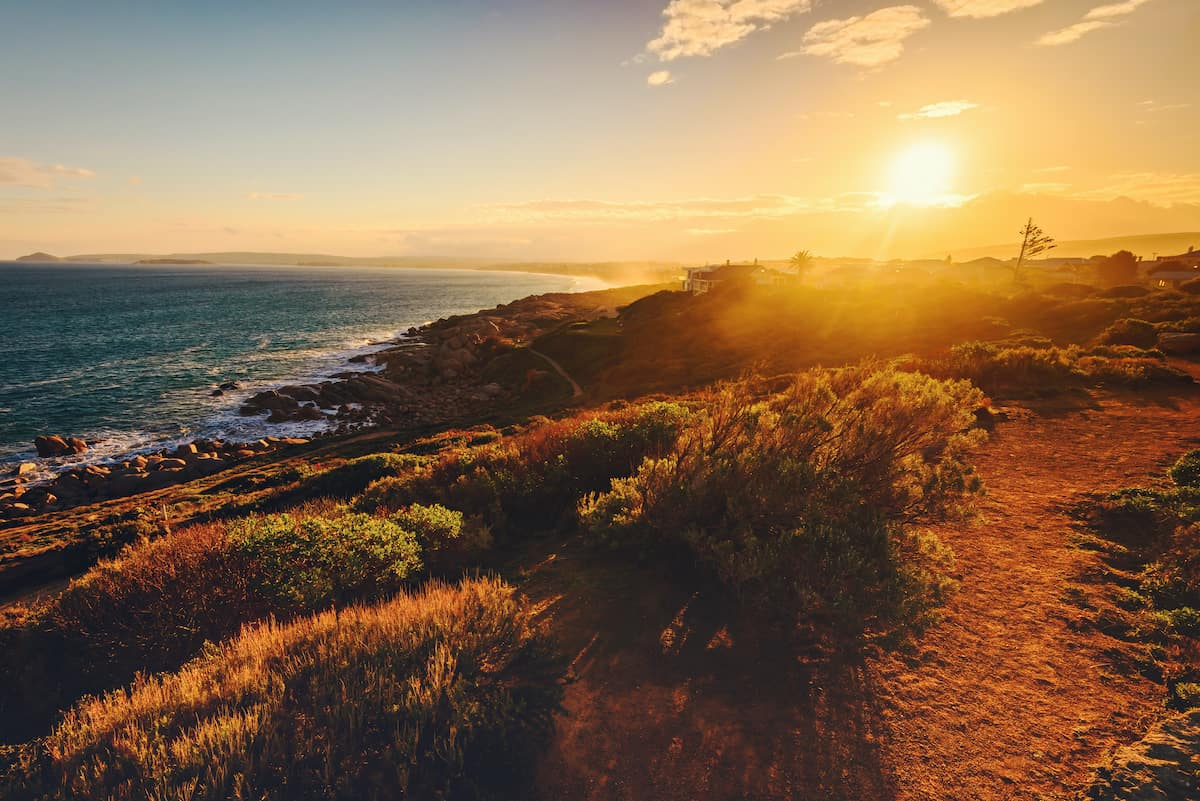 Sunset over a coastal path with the ocean at the base of the cliffs on the left